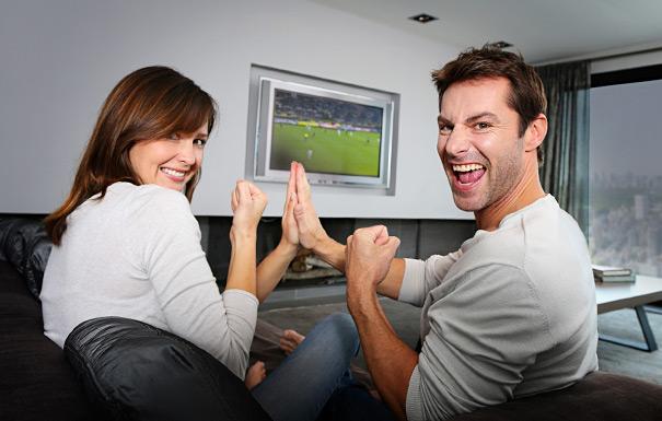 テレビでサッカー観戦するカップル