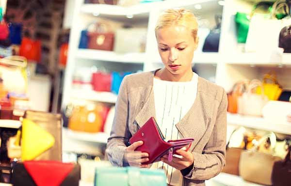 買い物中に財布の中を見る女