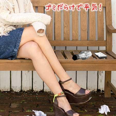 ゴミだらけのベンチに座る女性