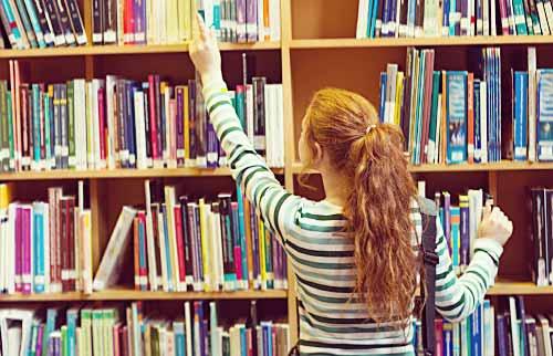 本棚から本を取る女性