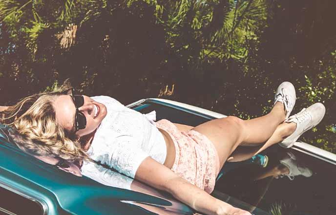 車の上に寝そべる女性