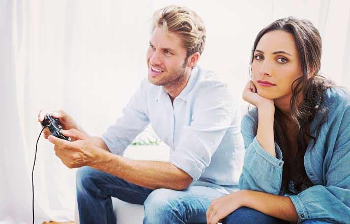 ゲームを楽しむ彼氏に呆れる女性