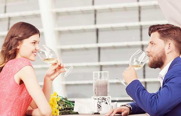 向かいあい、ワインを飲む男と女