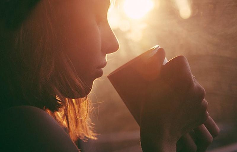 窓辺でコーヒーを飲む女子