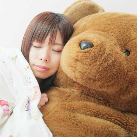 ぬいぐるみと寝る女性