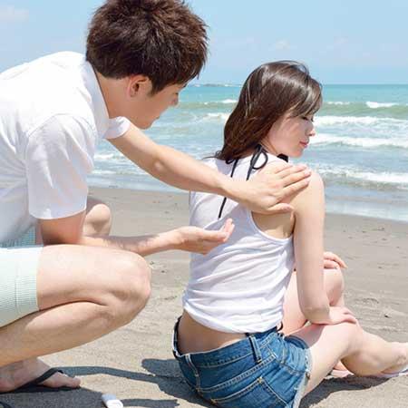 彼女の背中にオイルを塗る男性