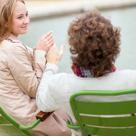椅子に座り手を握り合う男女