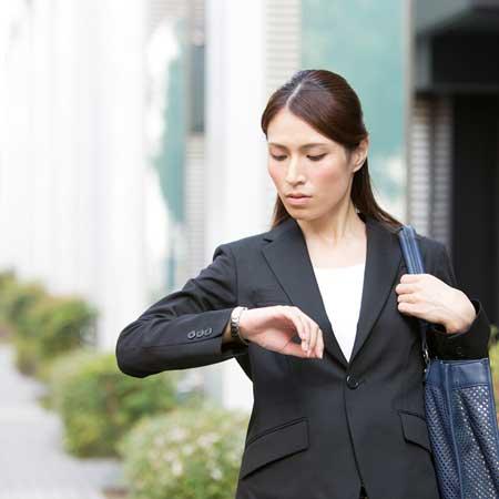 出勤時に腕時計を見る女性