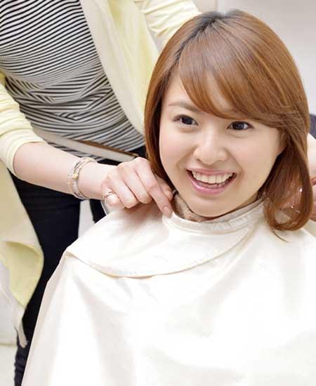 美容室で髪をカットしてもらう女性