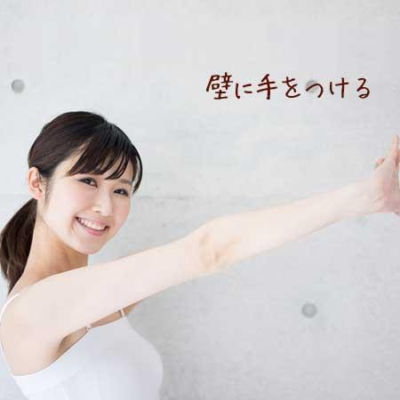 壁に手を押し当てる女性
