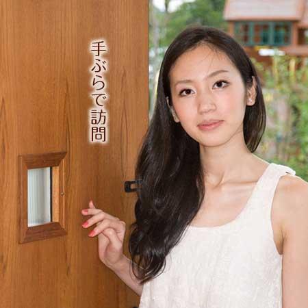 玄関のドアを開けて立つ女性