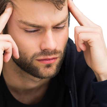 頭を指で押さえて沈黙する男性