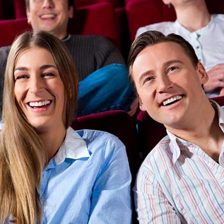 笑いながら映画鑑賞するカップル