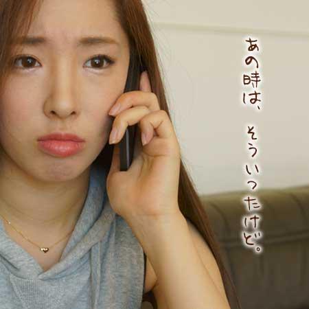 悲しい顔でスマホで電話している女性