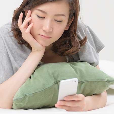 寝そべりながらスマホを見つめる女性