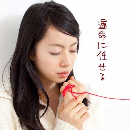 赤い糸を指につけながら目を閉じる女性