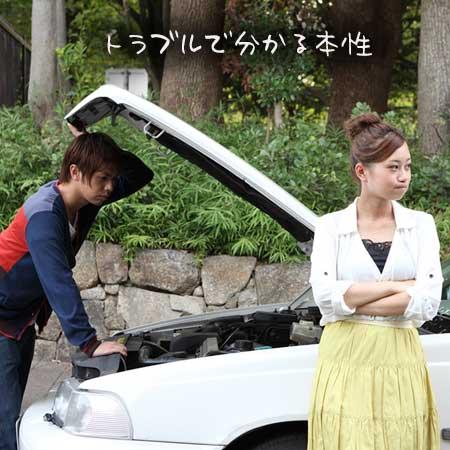 故障した車の前で不満顔の女性とエンジンを見る男性