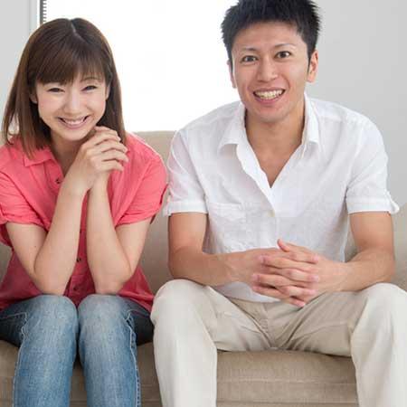 ソファに座り男性と談笑している女性
