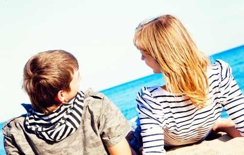 ビーチで楽しく会話するカップル