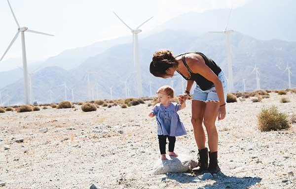 子どもと風車を見る女性