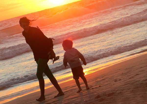 夕日の砂浜で歩く女性と子供