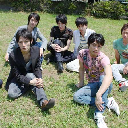 芝生に座っている男性達