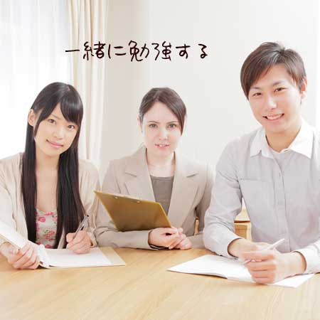 語学教室で男女、真ん中に先生を挟んで勉強する