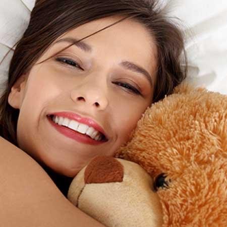 ぬいぐるみを抱きながら微笑む女性