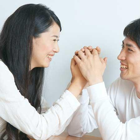 彼氏に手を握られて笑顔の女性