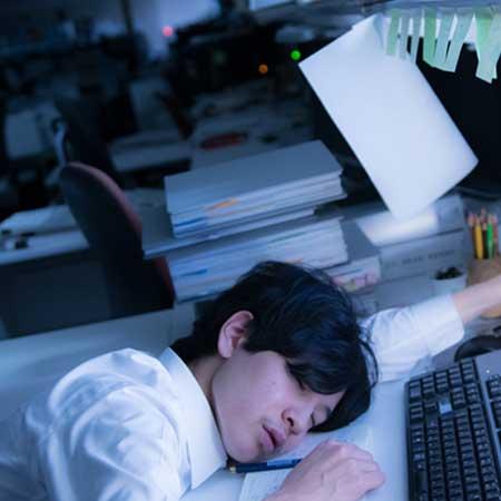 残業で居眠りしている男性
