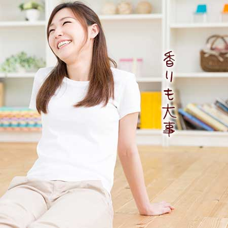 フローリングの上に座りながら笑顔の女性