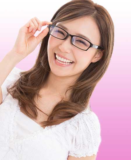 四角フレームのメガネに手をかけながら笑う女性