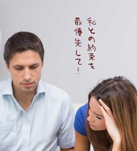 彼氏の傍らに座りながら頭を抱えこむ女性