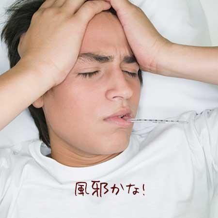 頭を抱えて熱を計る男性