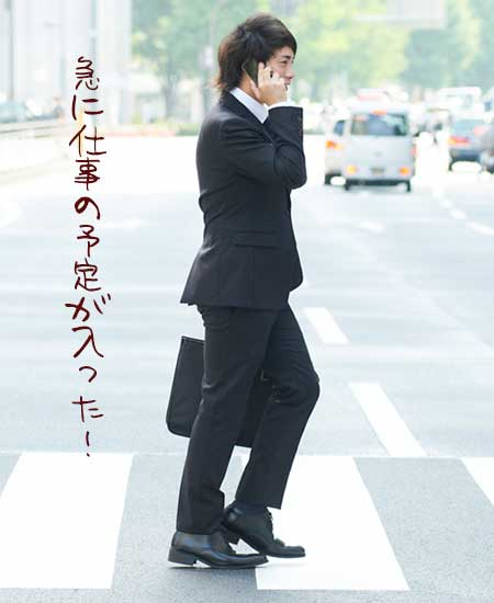 仕事電話を受けながら歩く男性