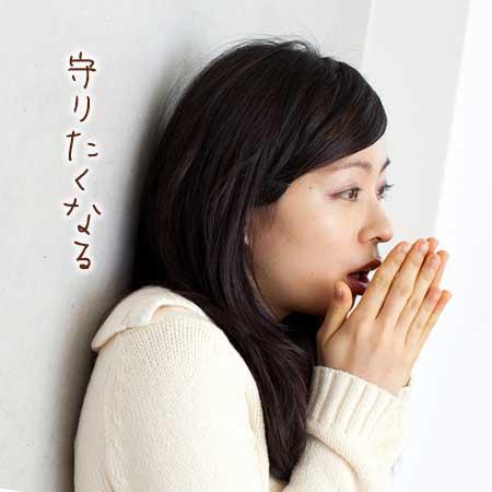 寒そうに手に息を吹きかけている女性