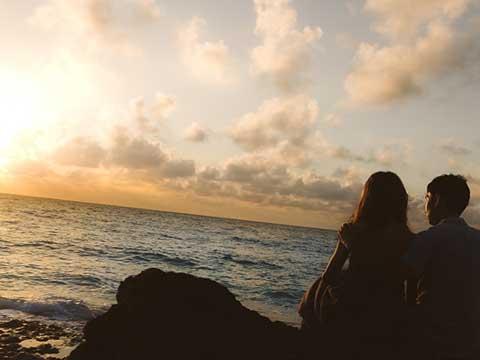 海岸の夕日と男女