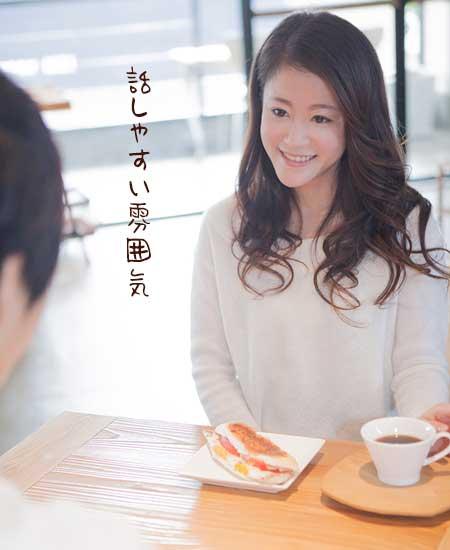 喫茶店で彼と向かいあいながら笑顔の女性