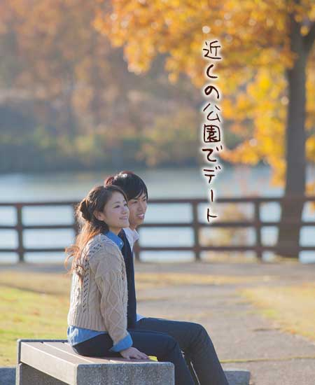 紅葉の公園でベンチに座る男女
