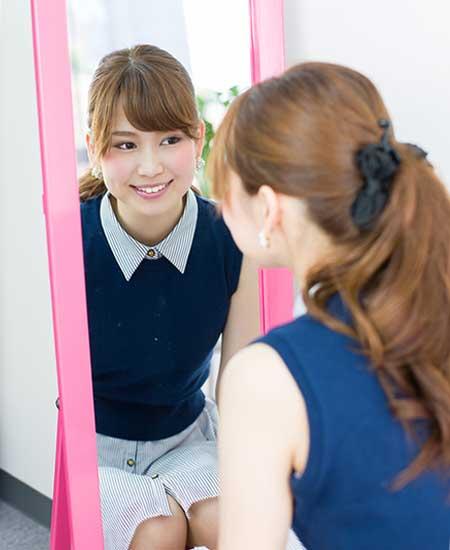姿見鏡に自分を映す女性