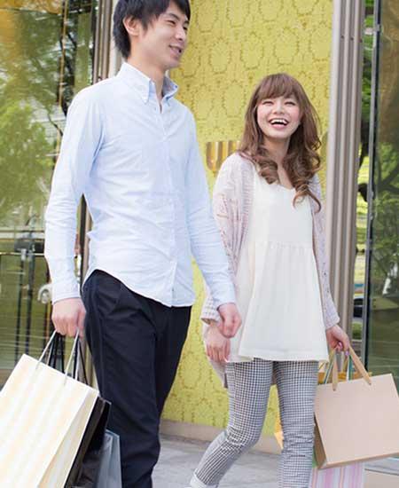 ショッピングバックを下げて二人で歩いているカップル