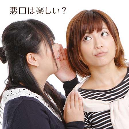 他の女性の耳元で何かを話す女性