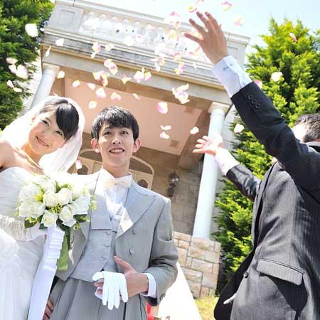 結婚式の新郎新婦に花をかける友人