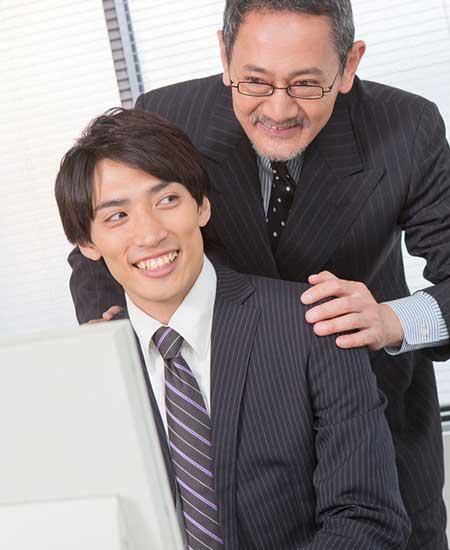 会社の上司に肩に手を置かれる男性