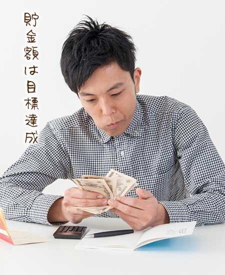 貯金通帳を開き紙幣を数える男性