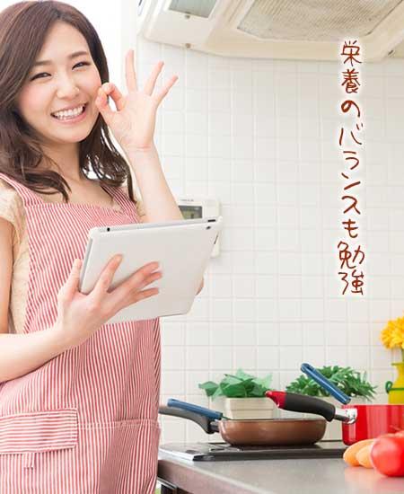 台所でタブレットを片手に料理する女性