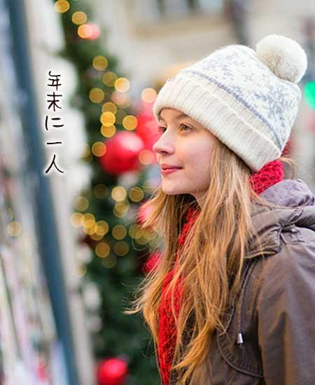 クリスマスに一人で街に立つ女性
