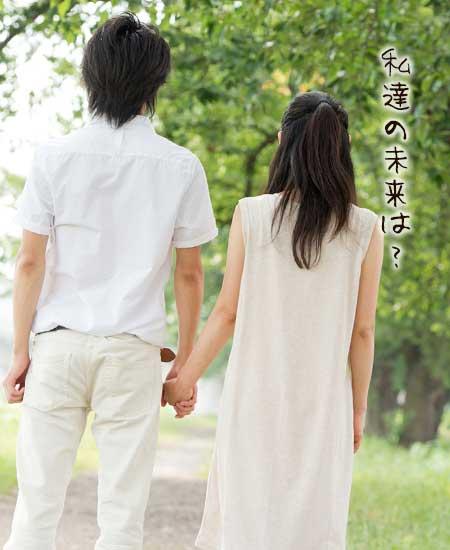 手を繋いで歩くカップルの後姿