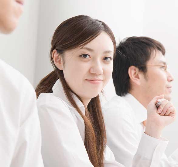 職場で同僚と席につく女性