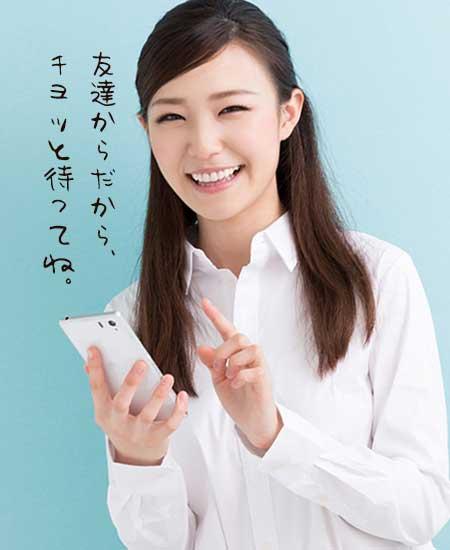 スマホを操作しながら笑顔の女性